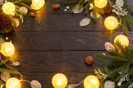 Christmas decorations with lights on dark wooden background