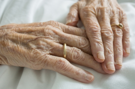 Closeup of wrinkled hands of an old woman lying in bed photo
