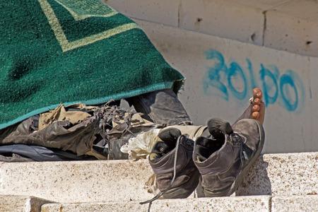 pieds sales: L'homme sans abri dormant � des �tapes � S�ville avec ses chaussures et les pieds sales