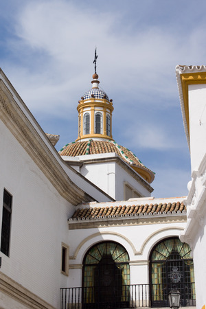 toros: View on a white church tower near the Plaza de Toros in Seville