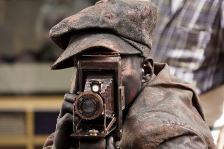 antiquary: ARNHEM; THE NETHERLANDS  30 SEPTEMBER 2012; Young man performing as a photographer at the World Statues Festival in Arnhem; that is yearly held in Arnhem in The Netherlands Editorial