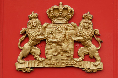orange nassau: A coat of arms  showing two lions holding a shield with a third lion on it and a crown.  Stock Photo