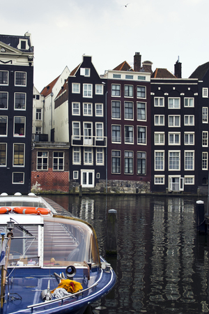 house float on water: View on typical Dutch warehouses in Amsterdam with with sightseeing tourism boat.