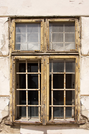 urban decline: Windows with bars in an abandoned house