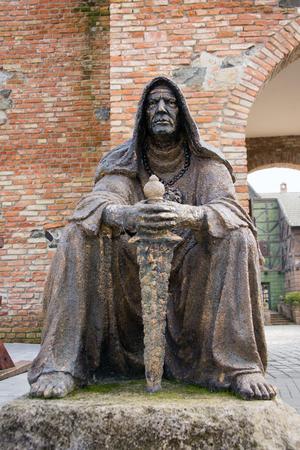 ahorcado: Estatua de un verdugo sentarse con su arma en un ambiente medieval