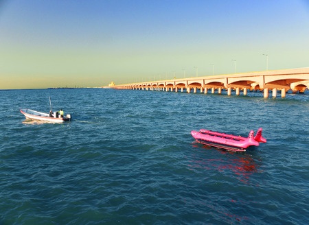 A small boat towing a rubber boat next to a large arch dock of Progreso, Yucatan, Mexico