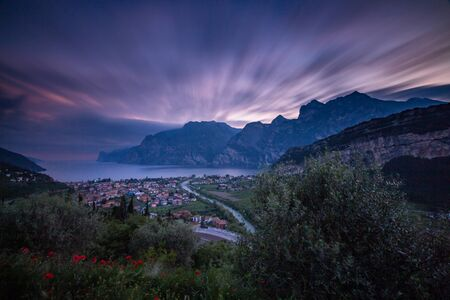 Long time exposure of evening sunset of Torbole, a colorful village at Lago di Garda (Lake Garda), Trentino, Italy; financial loss in tourism due to empty hotel rooms for Corona Virus pandemic