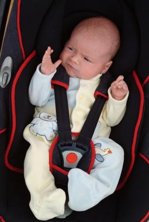 Een baby zit in een autostoel. Stockfoto - 17574278