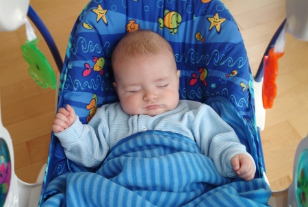 A baby boy is sleeping in a swing.