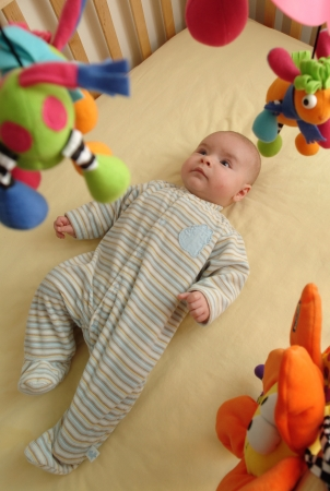 Baby is excited by a colorful mobile. photo