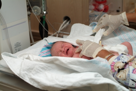 a nurse is swaddling newborn in hospital photo