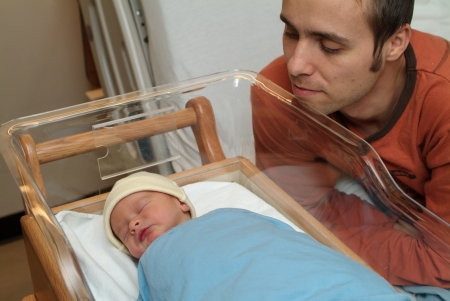 father is looking at newborn baby in hospital photo