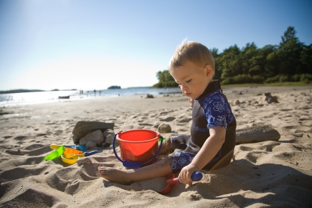 toddler playing with shovel and bucket at beach photo
