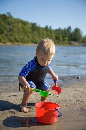 toddler playing with shovel and bucket at beach