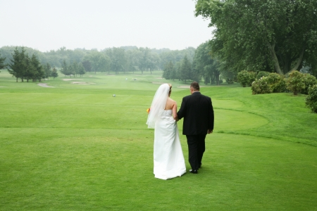 wedding couple walking at a golf course photo
