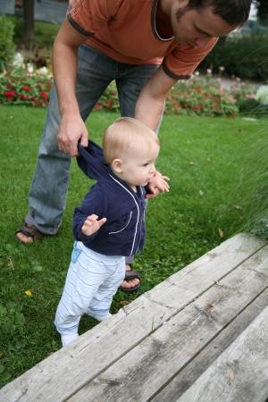 teaches: Father teaches child to walk  Stock Photo