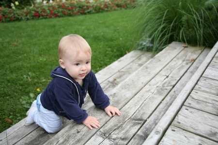 bebé está gateando y subir las escaleras fuera Foto de archivo