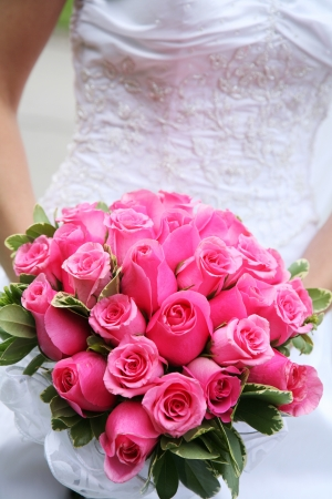 A bride is holding a a bouquet of pink roses. Imagens
