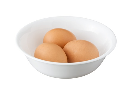 Three brown eggs in a bowl isolated on white background photo