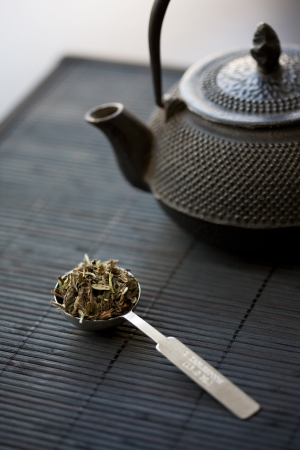 Spoon of green tea and teapot photo