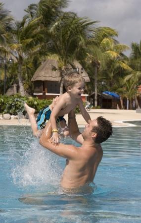 niño sin camisa: Padre e hijo que juegan en la piscina al aire libre en un centro turístico tropical Foto de archivo