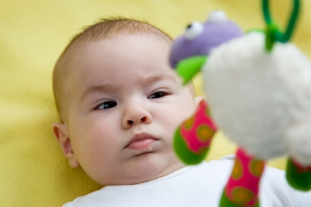 stimulate: Baby looking up at a mobile toy Stock Photo