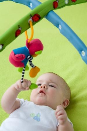 pull toy: Beb� agarrar un juguete que cuelga Foto de archivo