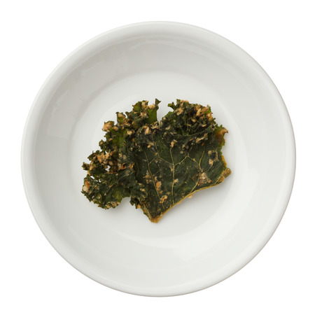 Roasted kale chips in a bowl isolated on white background photo