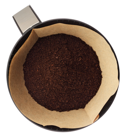 Ground coffee in filter holder isolated on white background overhead view