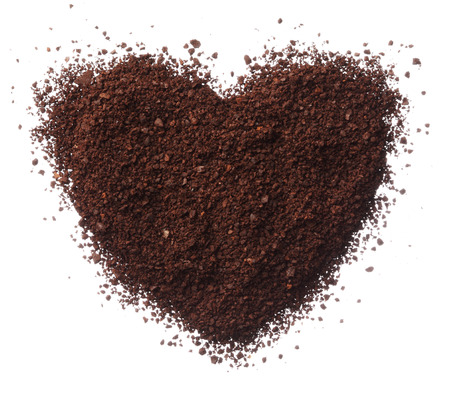 Ground coffee heart isolated on white background close up