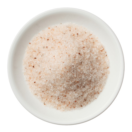 Himalayan pink salt pile in a plate isolated on white top view photo