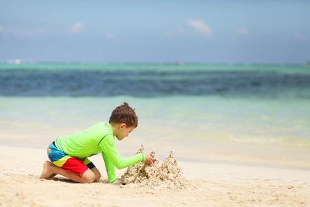 chateau de sable: Caucasien ch�teau de sable de construction de gar�on sur la plage tropicale