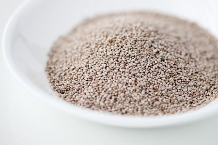 White chia seeds in a bowl against white background