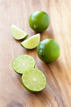 Green limes on a cutting board, close up