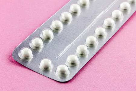birth control: Las p�ldoras anticonceptivas en un fondo de color rosa Foto de archivo