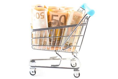 spending money: Little shopping cart full money -  spending money concept Stock Photo