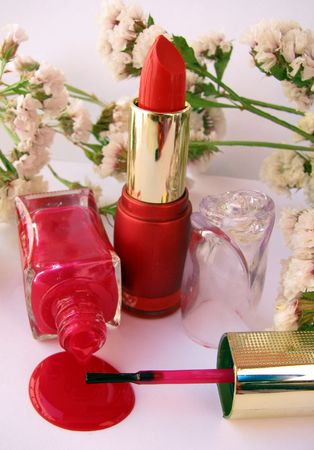 red lipstick and nail polish on white background photo
