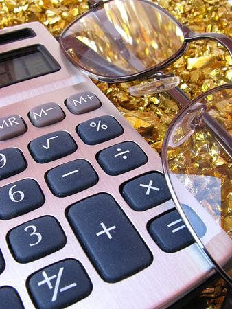Calculator and glasses on interesting gold background made of small gold rocks photo