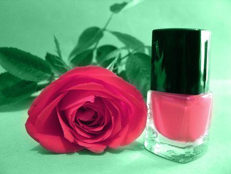 Pink rose and pink nailpolish on green background photo