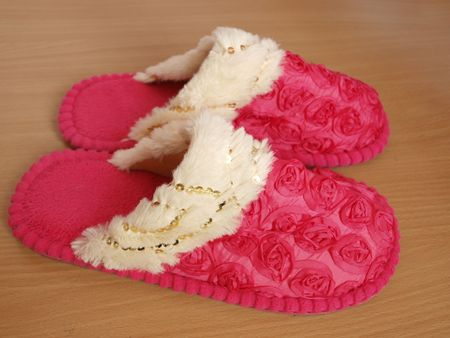 Pink home slippers  isolated on wooden floor photo