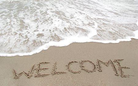 shoreline: bienvenida escrita en una playa tropical