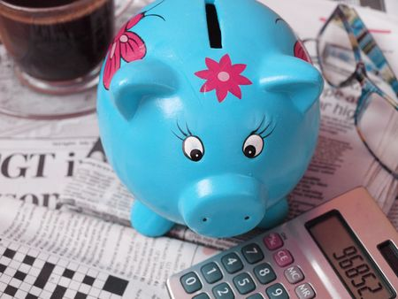 taxes budgeting: News,calculator, coffee,piggy bank and glasses-business concept
