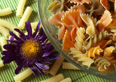 colored pasta  placed in glass plate and flower          photo