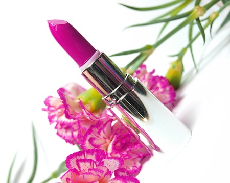 glamor shiny lipstick isolated on white background and flowers