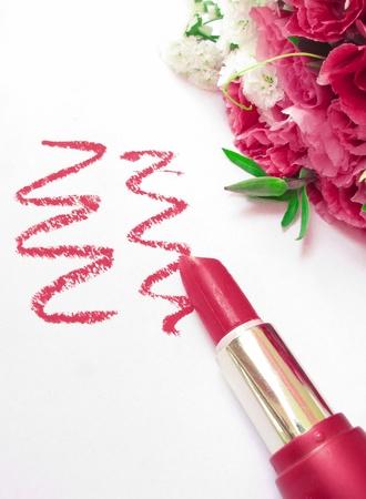 glamor shiny lipstick isolated on white background and flowers Stock Photo
