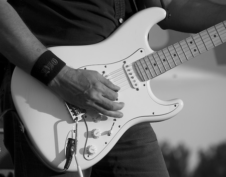 Man playing electrical guitar in black and white  photo