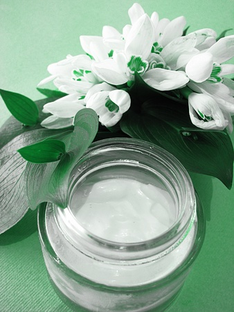 Facial cream with soft,white little flowers isolated on green background-beauty concept  photo
