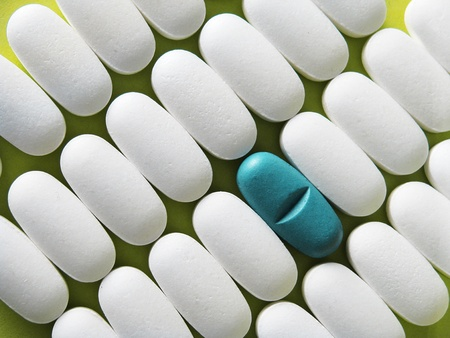 Spilled white and one blueblue pills isolated on green background  photo
