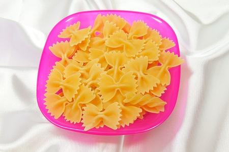 colored pasta on white satin photo
