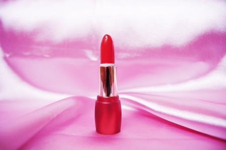 glamor shiny lipstick isolated on satin background  photo